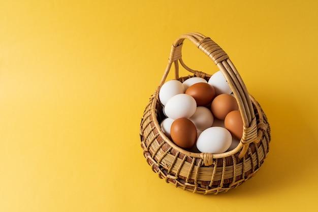 Eieren in een mand op gele achtergrond.