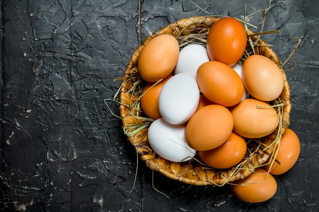 Eieren in een mand. op zwarte rustieke achtergrond.