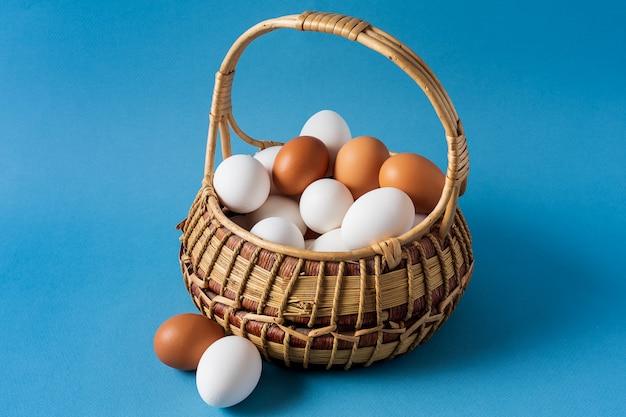 Eieren in een mand over blauwe achtergrond.