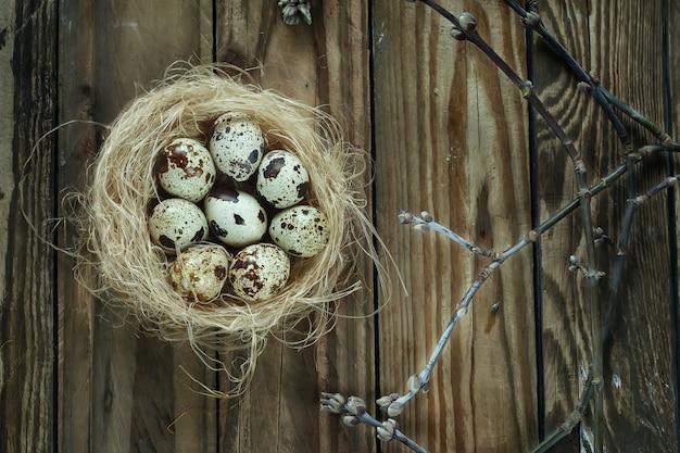 Eieren in een nest met takken op een houten tafel