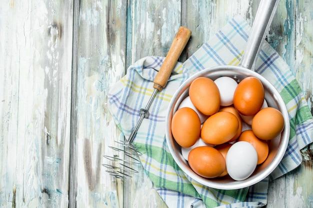 Eieren in een pan met een garde op servet. op een rustieke achtergrond.