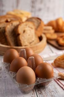 Eieren in een plastic panelen en brood dat op een witte houten plaat wordt geplaatst.