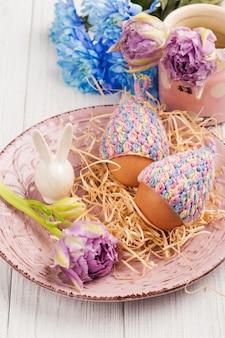 Eieren in gebreide mutsen, bloemen en decoratief konijn