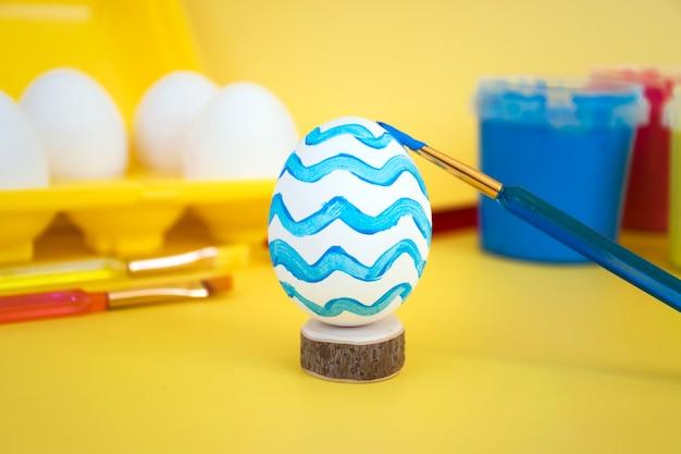 Eieren in geel eierrekje, kleurrijke verf en borstels om eieren te versieren voor vakantie. gezinsactiviteit, creatieve voorbereiding op vrolijk pasen.