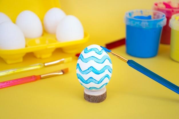 Eieren in geel eierrekje, kleurrijke verf en borstels om eieren te versieren voor vakantie