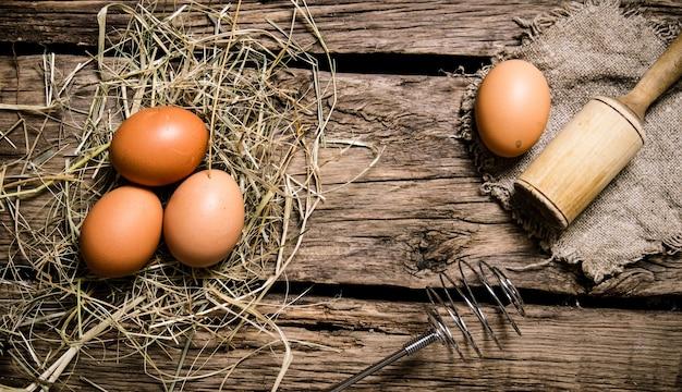 Eieren in het hooi met een stamper. op een houten tafel. bovenaanzicht
