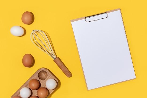 Eieren in houten eierdoos, garde en klembord met wit papier op gele achtergrond. platliggend bovenaanzicht mockup.