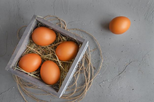 Eieren in houten kist met hooi op concrete achtergrond of oppervlak, concept van pasen of vakantie, bovenaanzicht, plat leggen