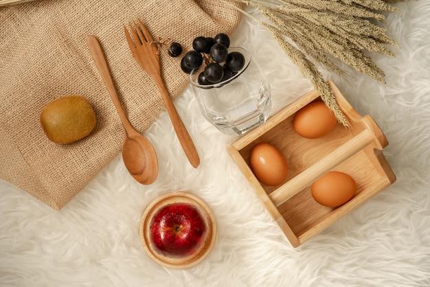 Eieren in houten mandje met verse, sappige rode appel op houten achtbaan.