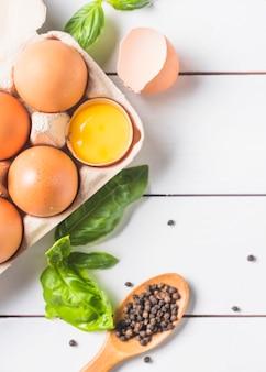 Eieren in karton met basilicumblad en peperbollen op houten plank