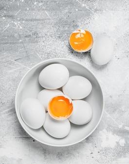 Eieren in kom. op een rustieke achtergrond.