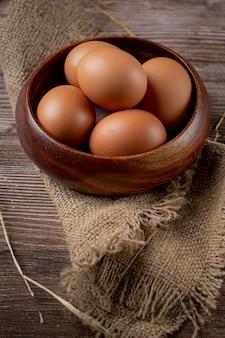 Eieren in kopjes op jute met droog gras.