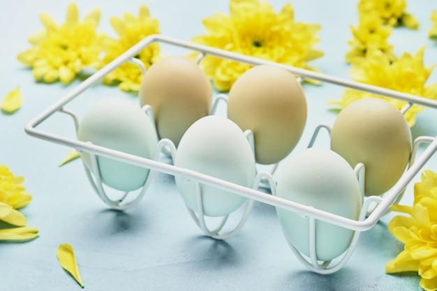 Eieren in witmetalen houder en bloemen op blauwe tafel. bovenaanzicht