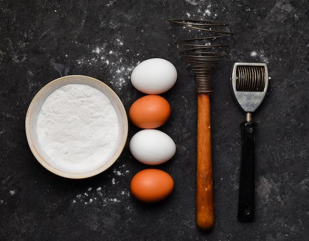 Eieren, meel, keukengerei op een zwarte betonnen tafel. ingrediënten voor pasta. het kookproces. hulpmiddelen om te koken. italiaanse keuken. bovenaanzicht. plat leggen.