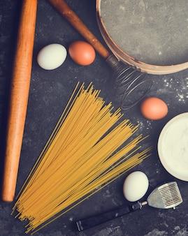 Eieren, meel, pasta en keukengerei op tafel