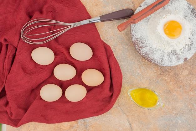 Eieren met olie en klop in het rode oppervlak