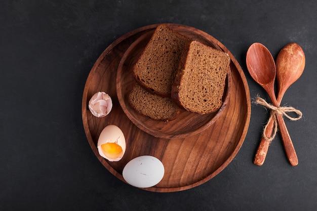 Eieren met sneetjes brood in een houten schotel, bovenaanzicht.