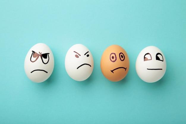 Eieren met verschillende emoties op zijn gezicht. pasen-samenstelling met exemplaarruimte op blauwe achtergrond.