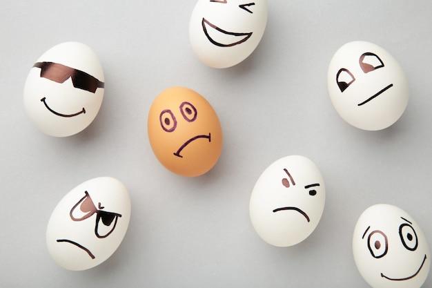 Eieren met verschillende emoties op zijn gezicht. pasen-samenstelling met exemplaarruimte op grijze achtergrond