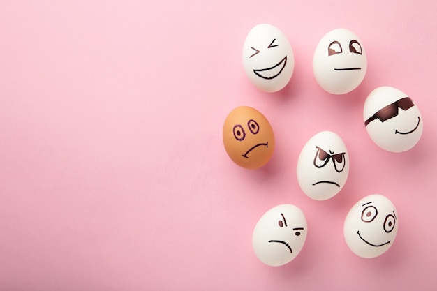 Eieren met verschillende emoties op zijn gezicht. pasen-samenstelling met exemplaarruimte op roze achtergrond.