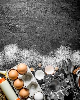 Eieren met vormen voor het bakken van het deeg op zwarte rustieke tafel