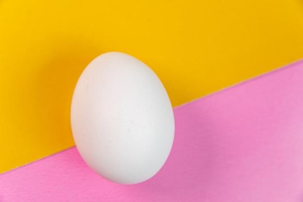 Eieren op de gele en roze achtergrond Gratis Foto