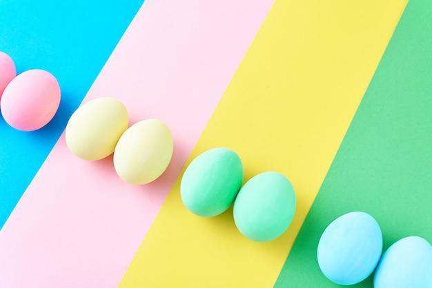 Eieren op gekleurde gestreepte achtergrond, minimalismconcept