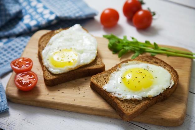 Eieren op sneetjes volkoren brood met rucola en tomaten op een houten bord