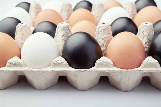 Eieren van verschillende kleuren in kartonnen dozen. zwart, wit en bruin kippeneieren.