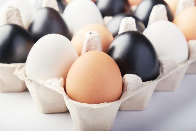 Eieren van verschillende kleuren in kartonnen dozen. zwarte, witte en bruine kippeneieren.