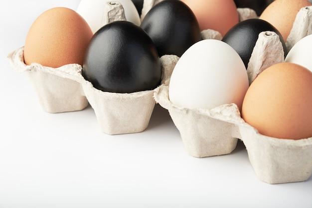 Eieren van verschillende kleuren in kartonnen dozen