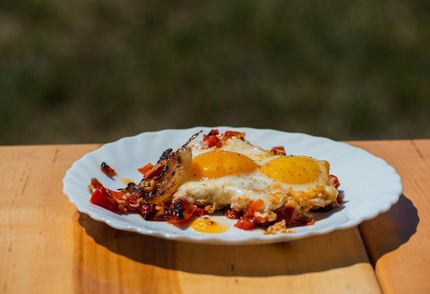 Eieren worden gebakken op een vuur op straat. gebakken eieren met spek. een gerecht van veel gebakken eieren op een kampvuur in de oven. straatvoedsel. rust uit met eten. gegrilde eieren in een pan