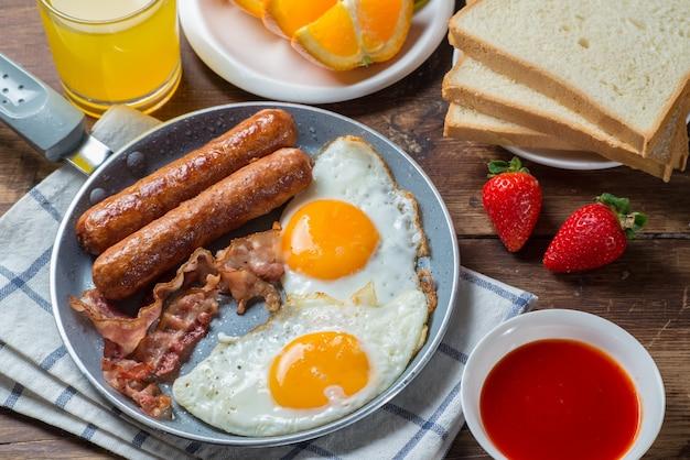 Eieren, worstjes, fruit, brood, sinaasappelsap in de pan