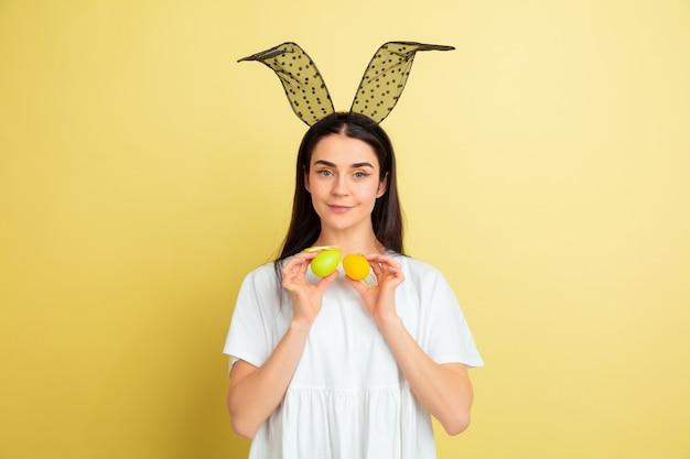 Eierenjacht komt eraan. blanke vrouw als paashaas op gele studioachtergrond. gelukkige pasen-groeten. mooi vrouwelijk model. concept van menselijke emoties, gezichtsuitdrukking, vakantie. copyspace.