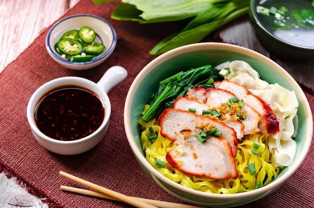 Eiernoedel met geroosterd rood varkensvlees, geserveerd met lokale zoete saus en witte sesam en groene chili in azijn