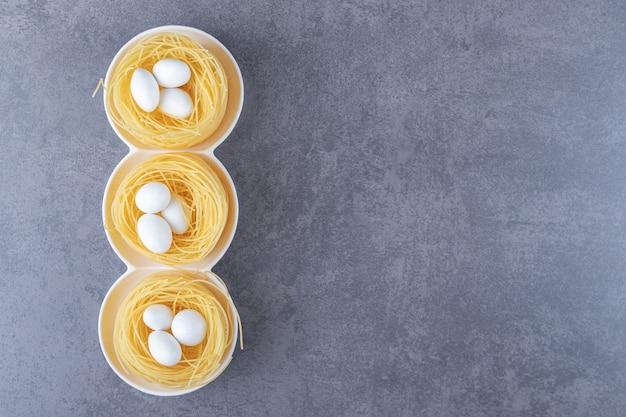 Eiernoedelnesten met witte snoepjes in kommen.