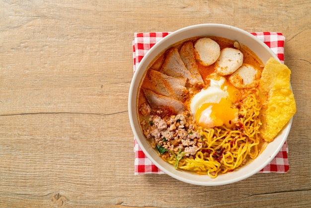 Eiernoedels met varkensvlees en gehaktbal in pittige soep of tom yum noodles in aziatische stijl