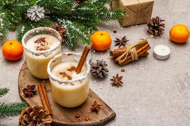 Eierpunch met kaneel en nootmuskaat voor kerst- en wintervakantie. zelfgemaakte drank in glazen met pittige rand. mandarijnen, kaarsen, cadeau.
