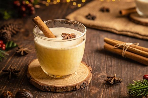 Eierpunch met pittige kaneel voor kerst- en wintervakanties gezellige cocktail met melk en kaneel en kruidnagelsterren traditionele kerstdrank met geraspte nootmuskaat en kaneel zelfgemaakte witte vakantie