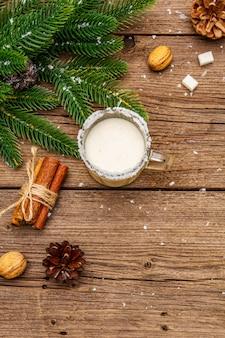 Eierpunchlikeur of cola de monococktail. klassieke winterdrank in glazen mok, xmas decoraties. groenblijvende takken, kaneel, walnoten, suiker.