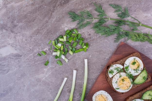 Eiersandwiches met komkommer en gehakte kruiden.