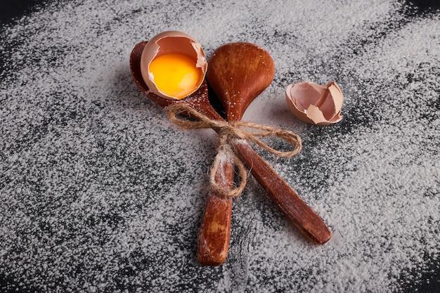 Eierschaal met dooier in een houten lepel.