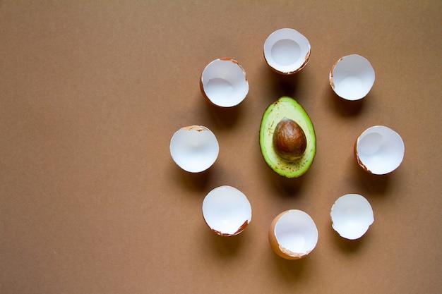 Eierschaal van weinig bruine kippeneieren rond de helft van rijpe avocado