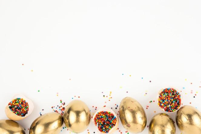 Eierschalen met hagelslag in de buurt van gouden eieren