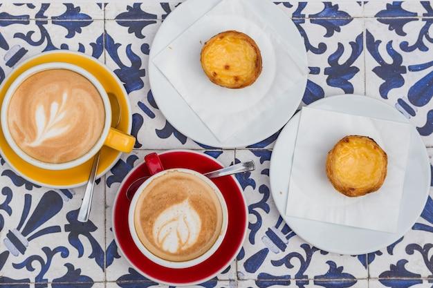 Eiertaart met koffie, traditioneel portugees dessert met latte en cappuccino, pastel de nata