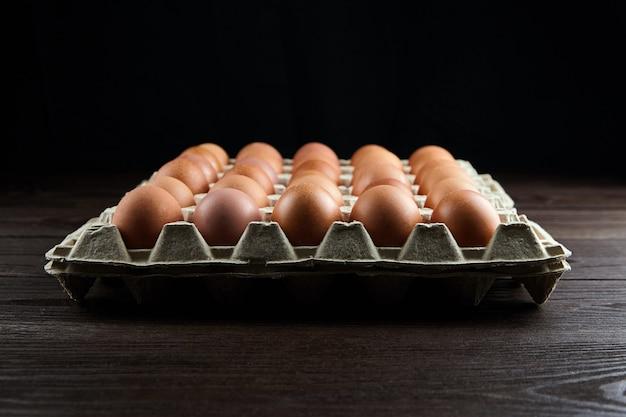 Eiertray op houten tafel. bruine kippeneieren in gerecyclede kartonnen verpakking op tafel