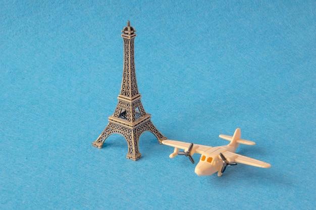 Eifeltorenmodel met weinig speelgoedvliegtuig op blauw