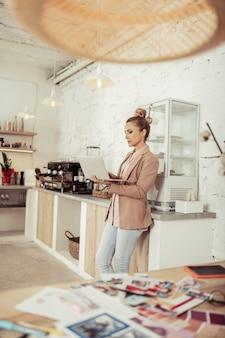 Eigen baas. mooie slimme vrouw die op haar laptop werkt die in de buurt van de grote tafel met koffiezetapparaat staat.