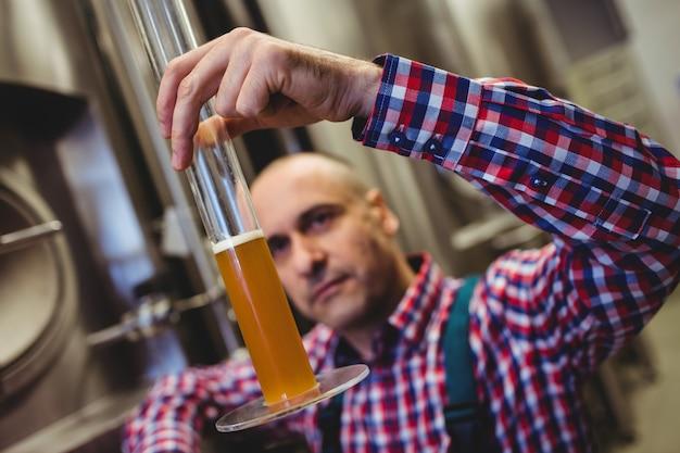 Eigenaar die bier in glazen buis onderzoekt