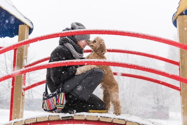 Eigenaar en haar hond kussen neus tijdens winterwandeling